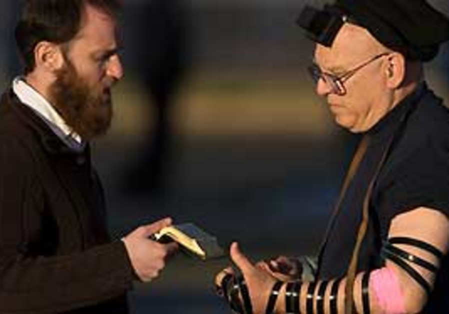 Rabbi Stanley Howard Schwartz, right, puts on tefi