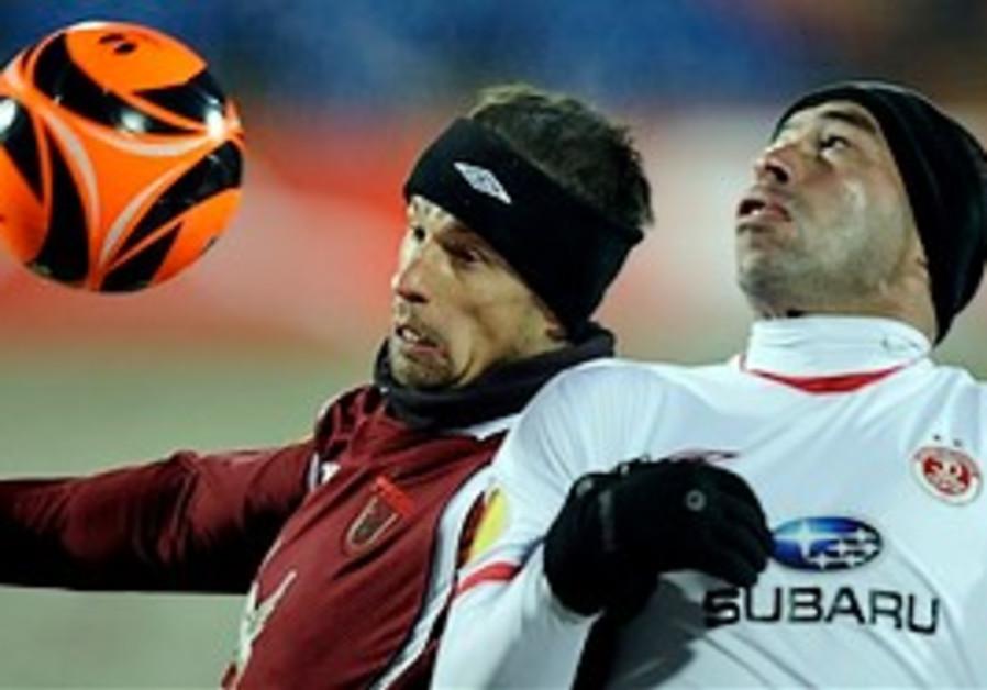 Rubin Kazan's Semak, left, vies for the ball with