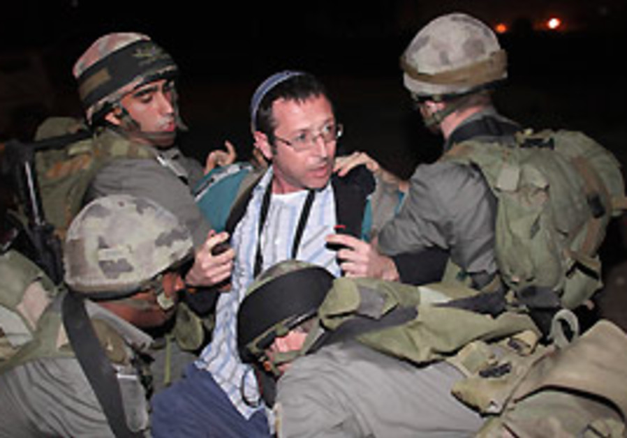 IDF soldiers detain a Jewish settler after he was