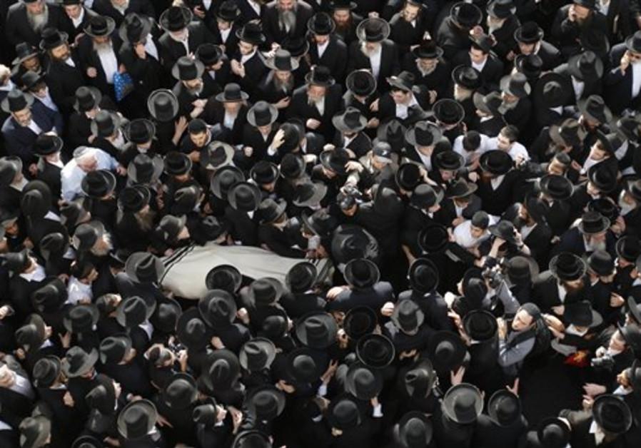 Orthodox Jewish men carry the body of Rabbi Menahe