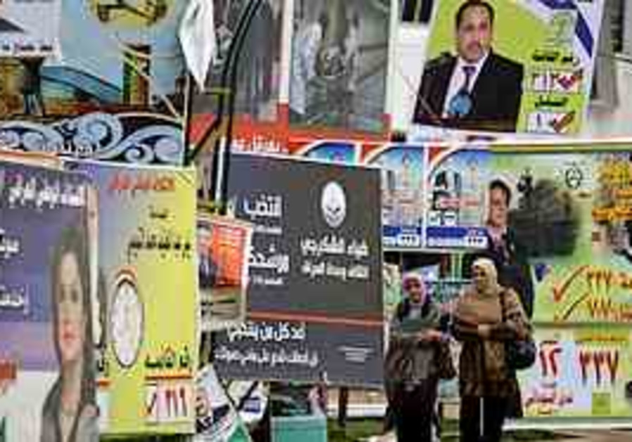 Iraqis walk past election campaign posters for can