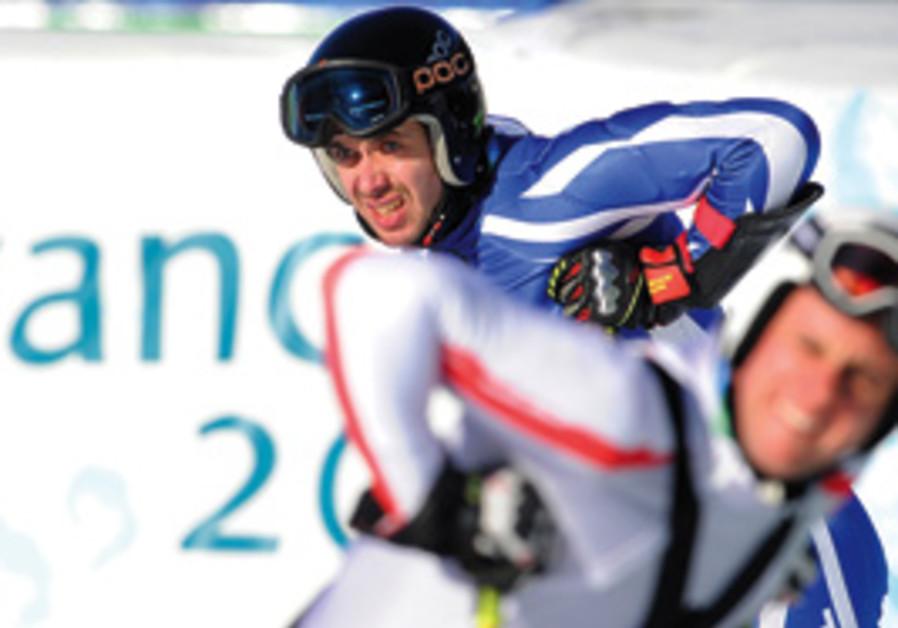 Israeli skier Mikhail Renzhin (rear) pauses in the