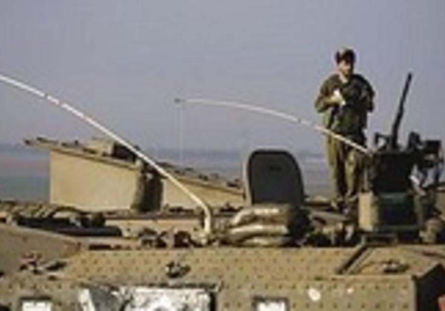 An IDF soldier atop an APC near the Gaza border fe