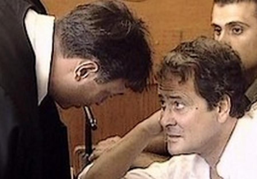"""Dudu Topaz (z""""l) talks to a judge in court."""