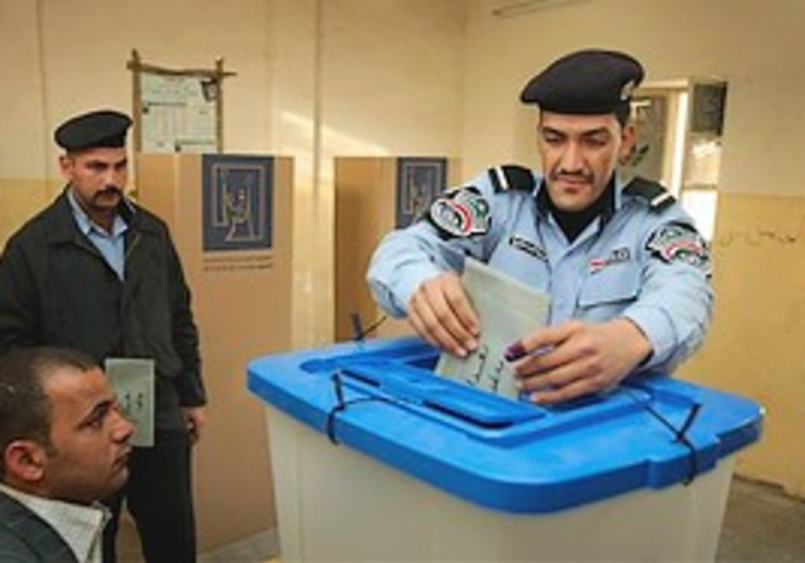 Iraqi police officer casts his vote at a polling c