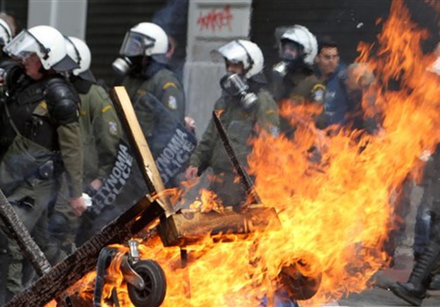 Riot police pass by a burning barricade set on fir