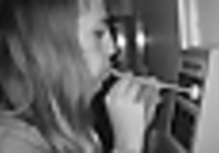 A woman takes a Breathalyzer test. [illustrative]