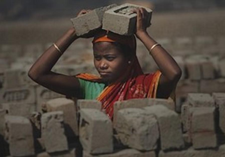 An Indian woman works at a brick kiln in Rajabari,