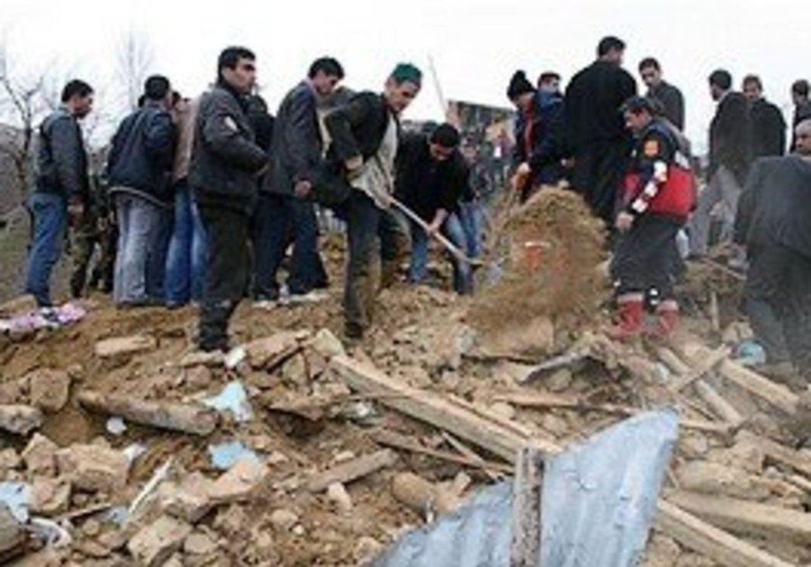 Rescue workers and people remove rubble from a des
