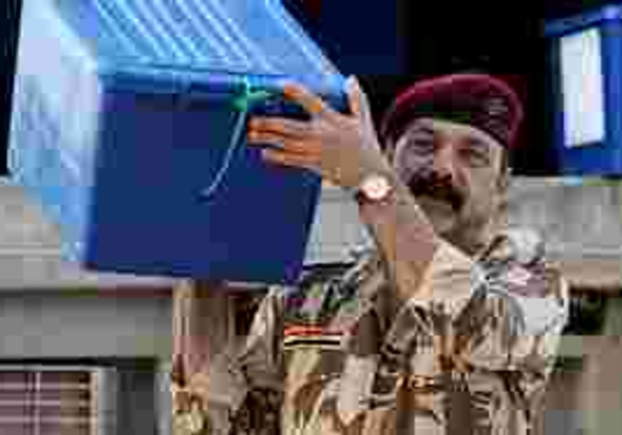 An Iraqi Army soldier carries a box of ballot tall