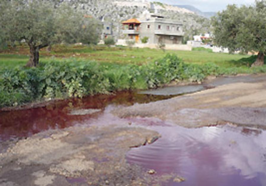 Blood-filled sewage flows in Majd el-Kurum's stree