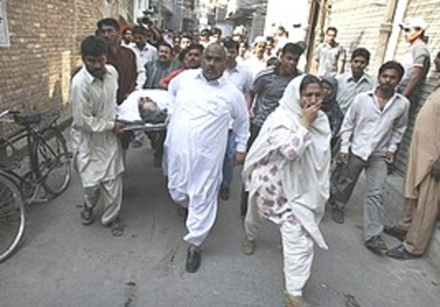 Locals carry the dead body of a suicide bombing vi