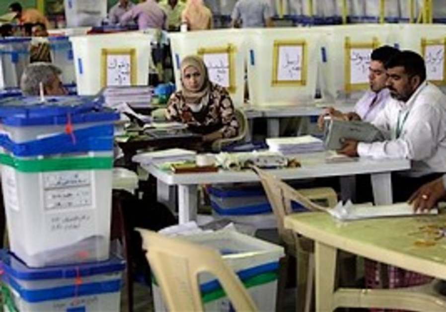Electoral workers sort through ballots cast at a c