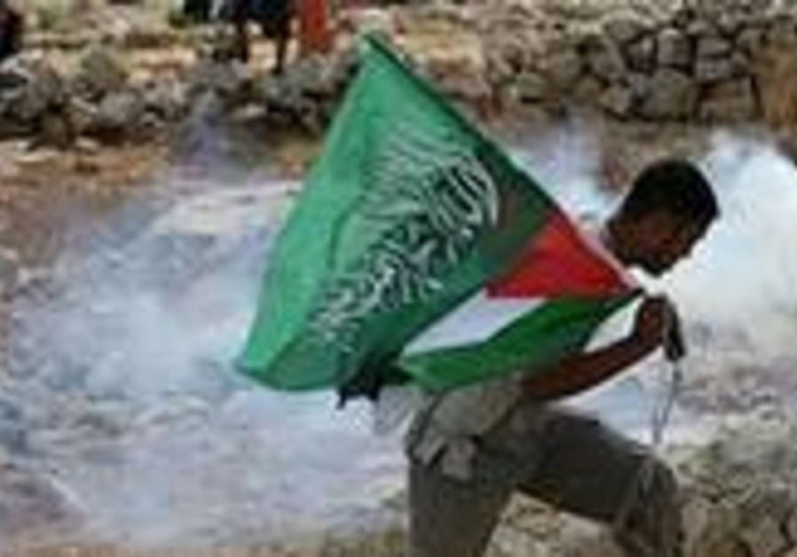 A Palestinian holds a green Islamic flag as he run