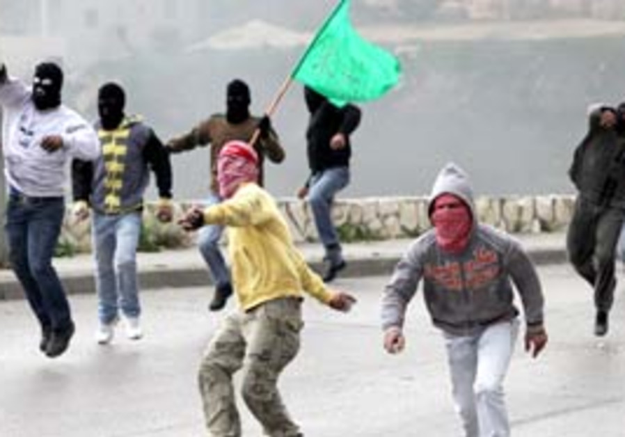 Palestinian stone throwers, some of them carrying