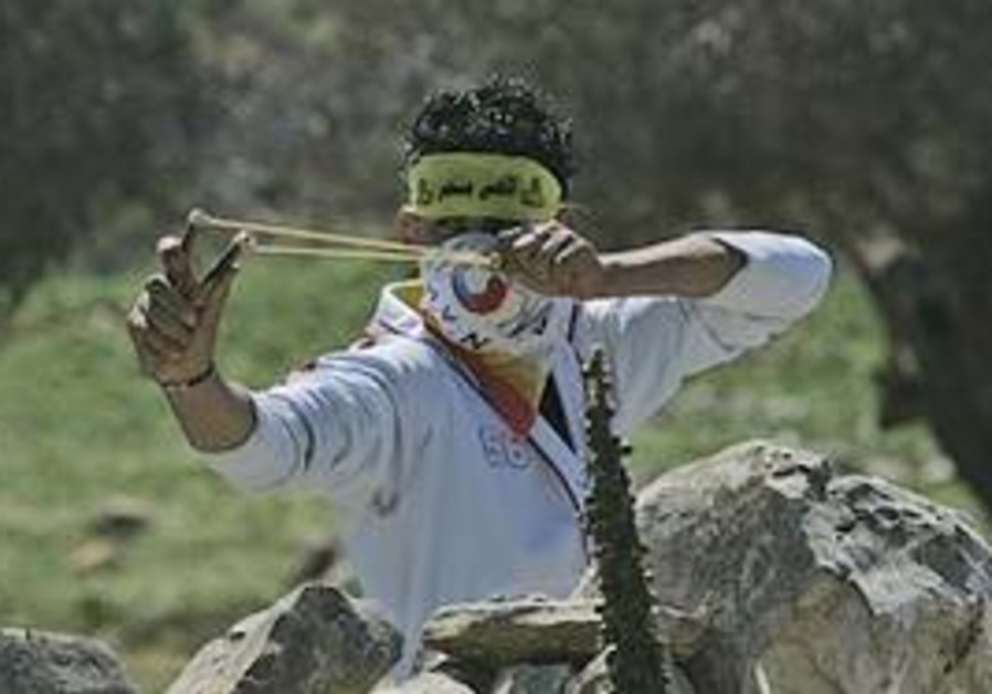 A Palestinian demonstrator uses a slingshot to hu