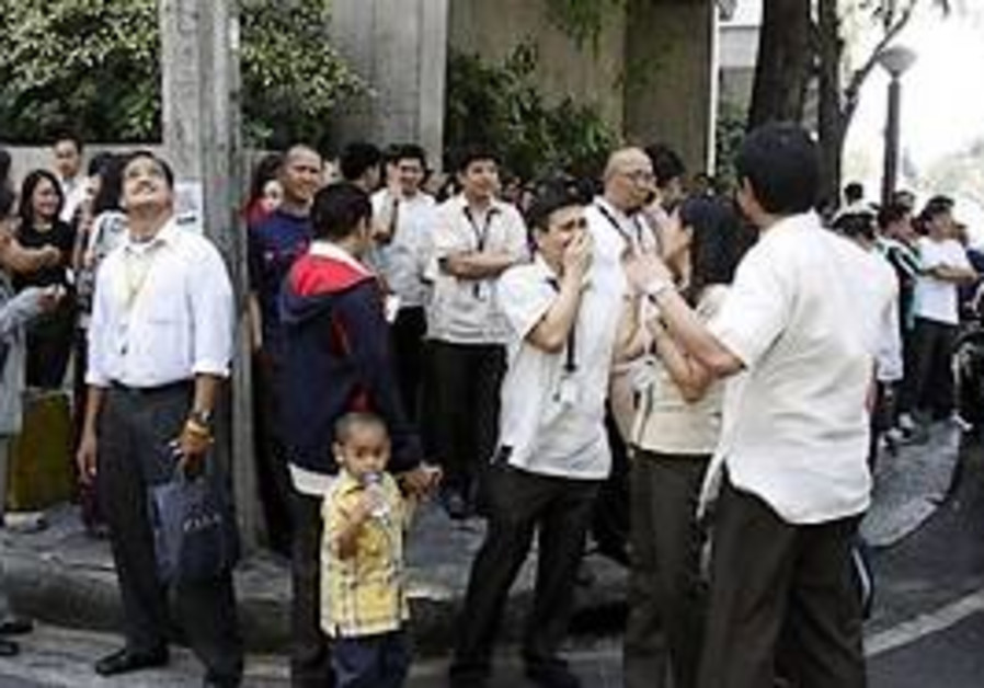 Employees gather on the side of a street after the