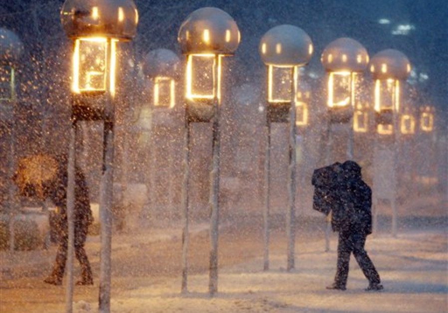Pedestrians struggle to hold on to their umbrellas