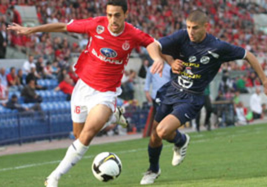 Hapoel Tel Aviv forward Eran Zehavi (left) runs pa