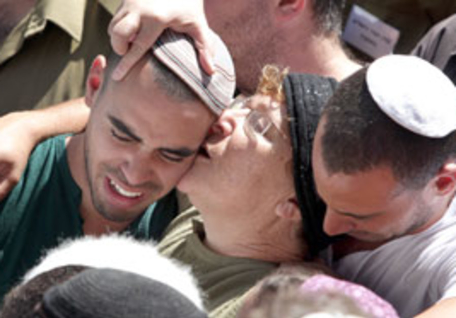 Miriam Peretz kisses her son Amichai during the fu