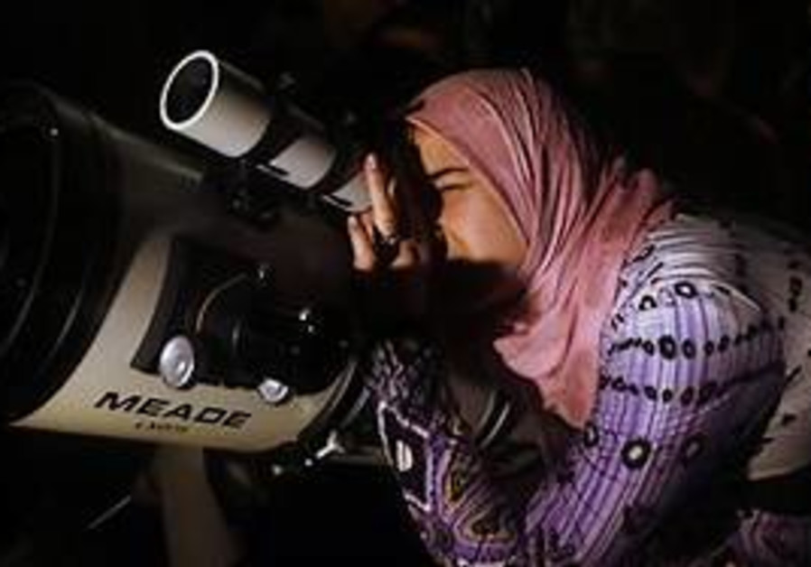 Palestinian girl looks through telescope during a