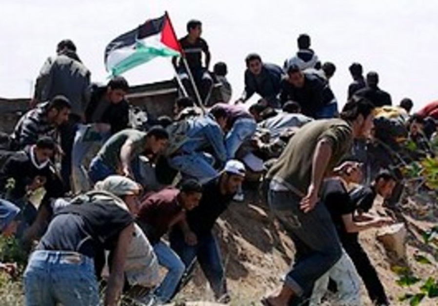 Palestinian youths take cover from IDF troops duri