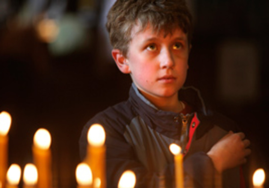 A boy crosses himself during a religious service f