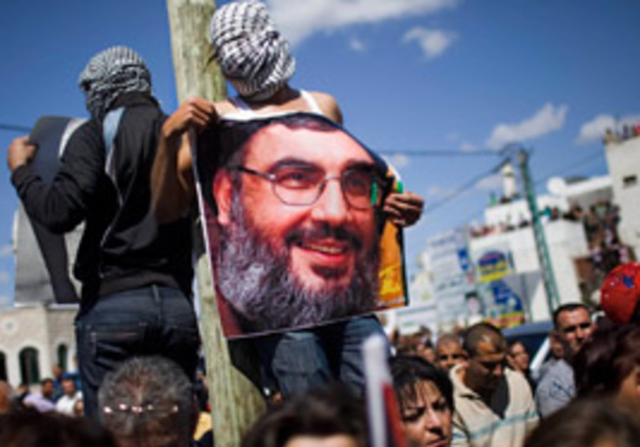 An Arab Israeli demonstrator displays a poster of