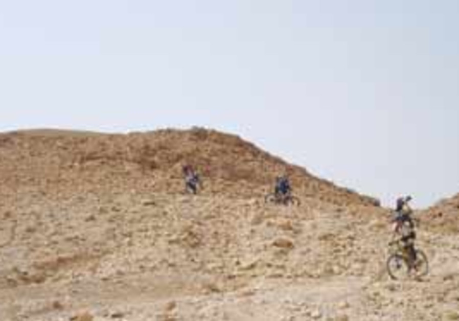 CYCLISTS RIDE among the dunes and rocks of the Neg