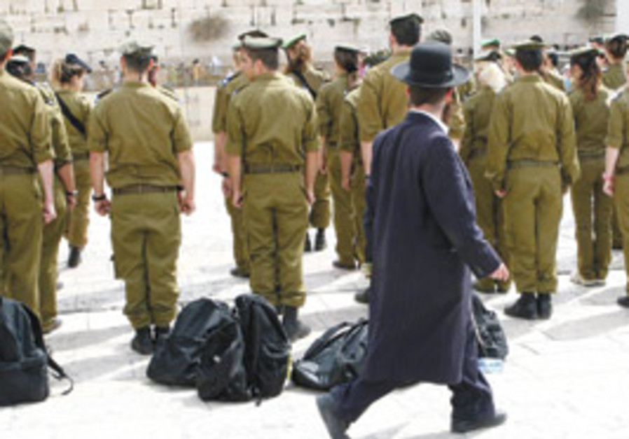 A haredi man walks past IDF soldiers