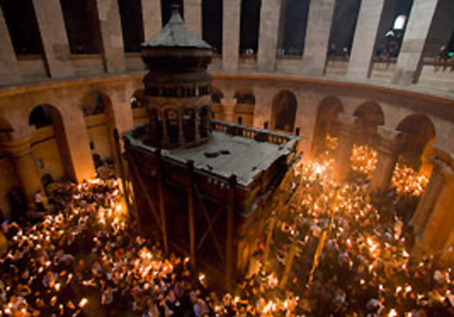 Orthodox Christian pilgrims hold candles at the Ch