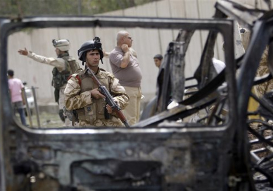 Iraqi security forces inspect the site of a car bo