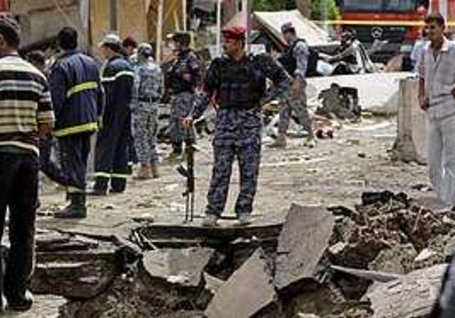 Iraqis inspect a crater caused by a car bomb attac