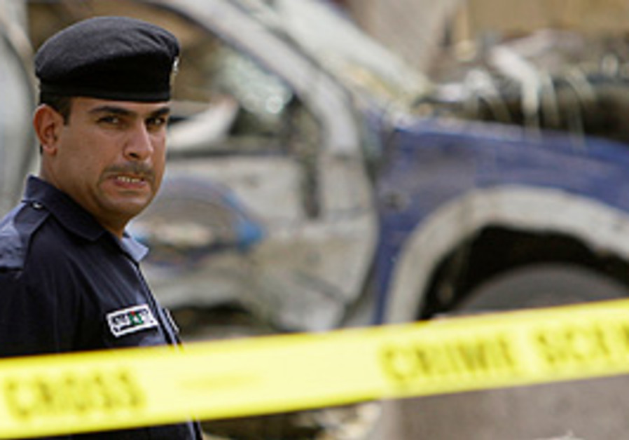 An Iraqi policeman reacts at the site of a car bom