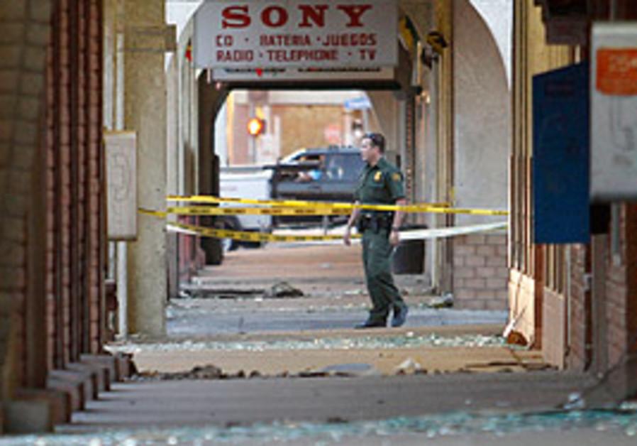 A US Border Patrol agent walks past rows of broken