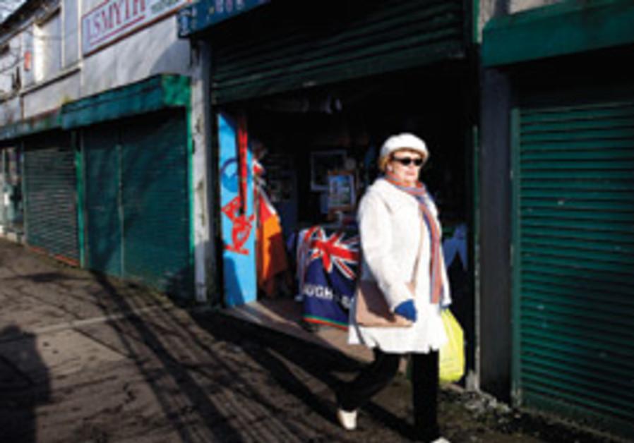 A WOMAN walks past boarded up shops in Belfast. As