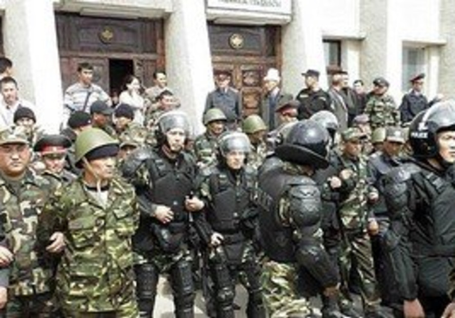 Kyrgyz police block off a government building befo