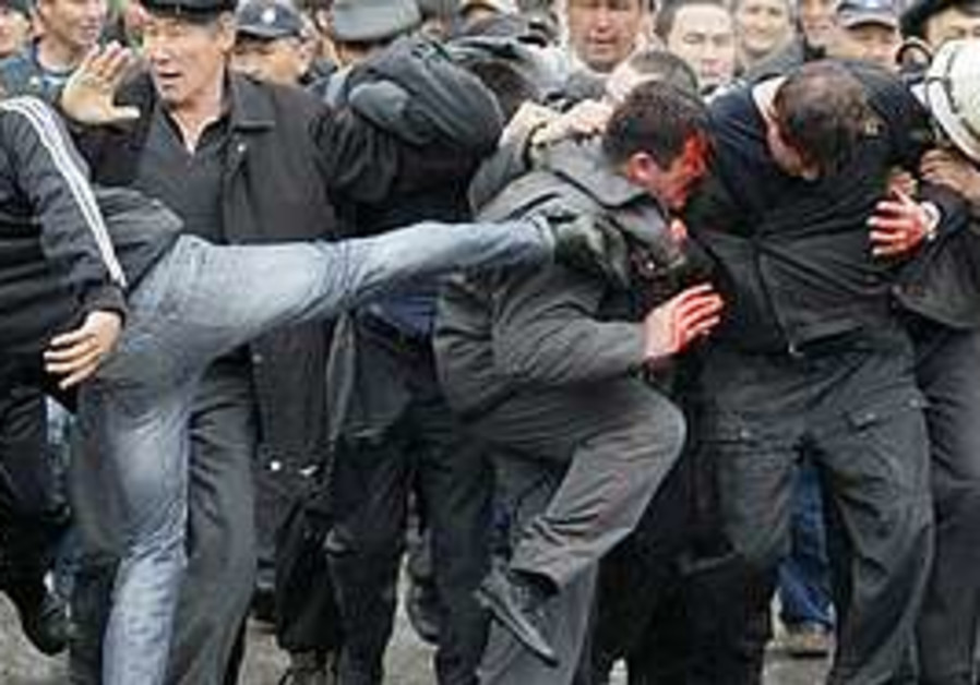 A Kyrgyz protester kicks out at captured police of