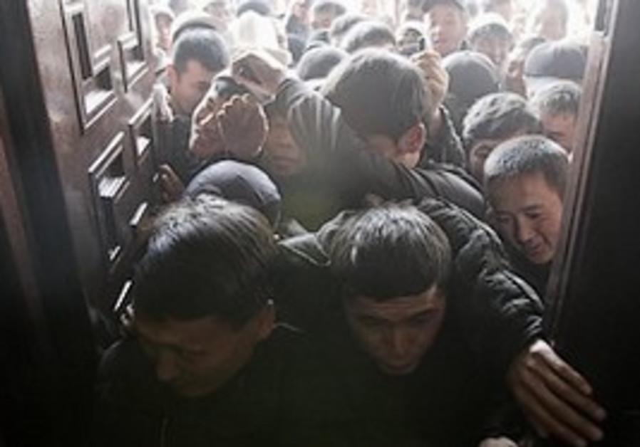 Protesters break through an entrance of Kyrgyz gov