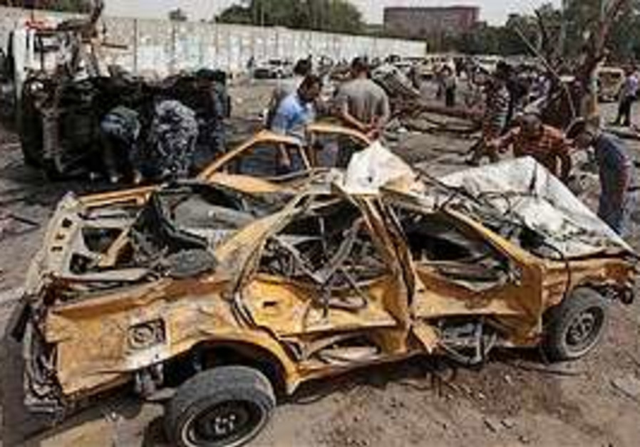 Iraqis inspect at the site of a car bomb attack ne