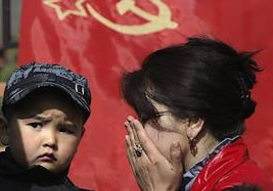 A Kyrgyz woman, right, with her son pray to mourn