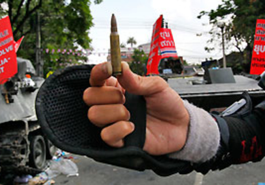 A Red Shirt guard shows people a bullet in front o