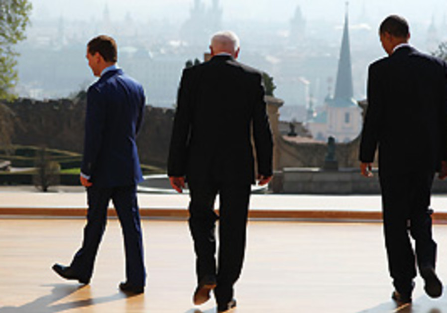 PRESIDENT BARACK OBAMA walks with Russian presiden