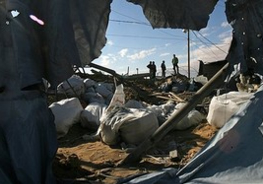 Palestinians examine a smuggling tunnel damaged in