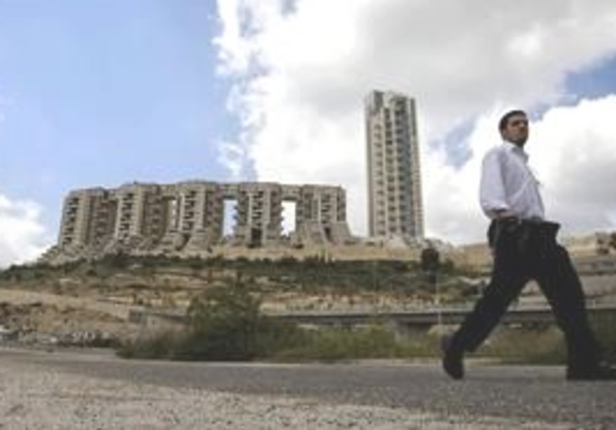 A  man walks past the Holyland real estate project