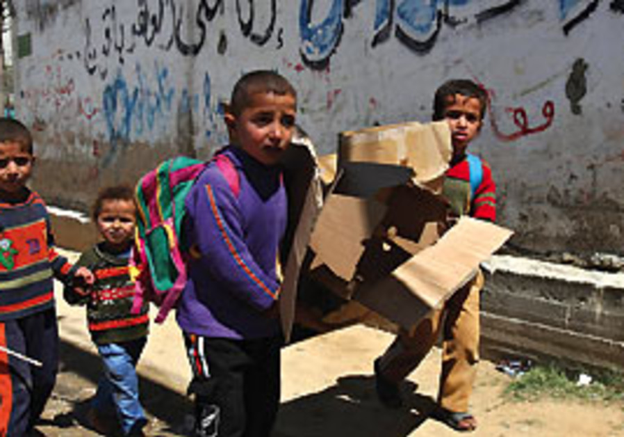 Palestinian children carry empty carton boxes to u