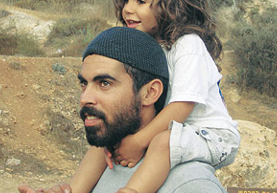 ELIRAZ WITH one of his four children, aged six and