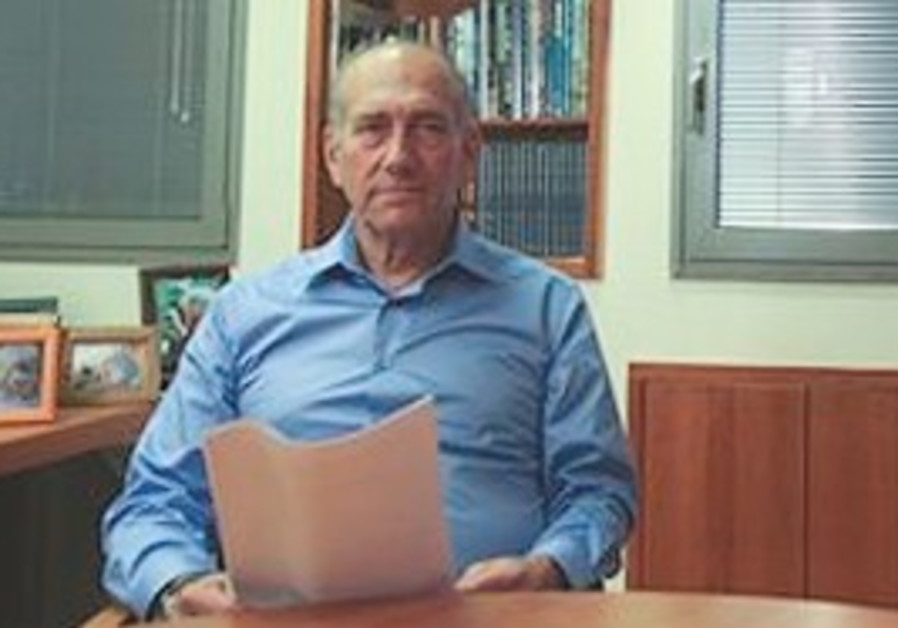 Olmert poses for the media before reading a statem