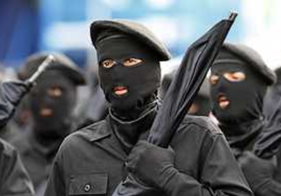 Masked Iranian army soldiers march during a parade