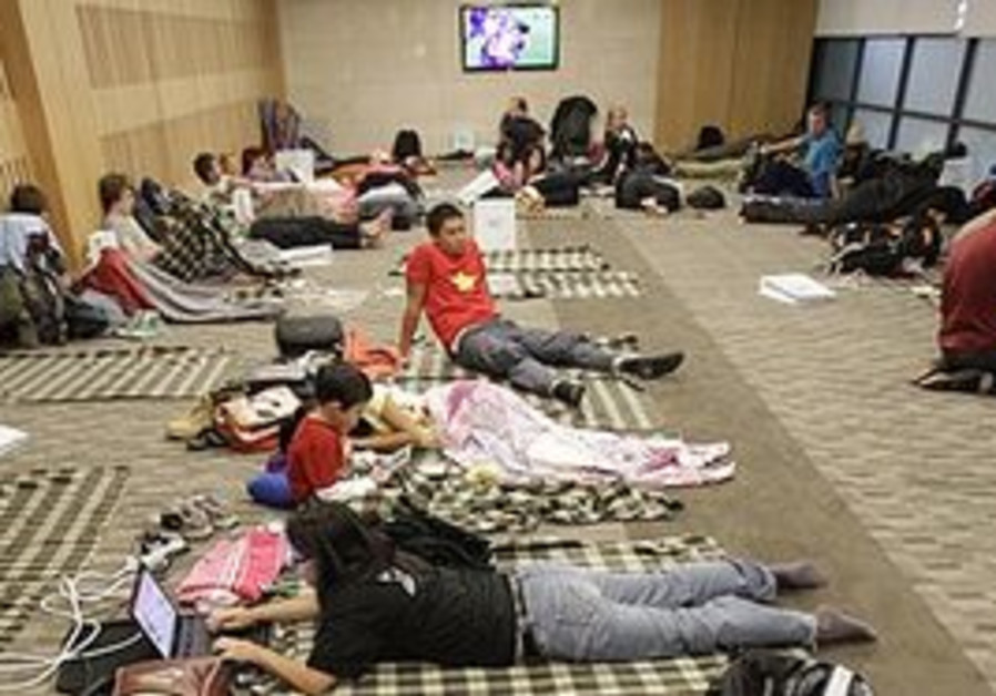 Passengers from Europe sleep as their flights for